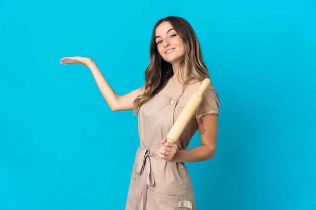 Giovane donna rumena che tiene un mattarello isolato su priorità bassa blu che estende le mani a lato per invitare a venire