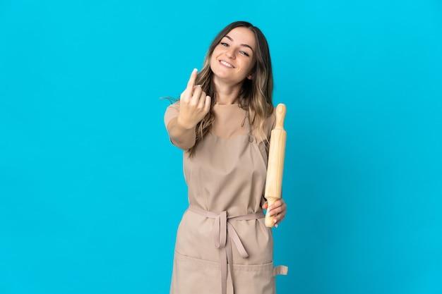 Giovane donna rumena che tiene un mattarello isolato sulla parete blu che fa gesto venente