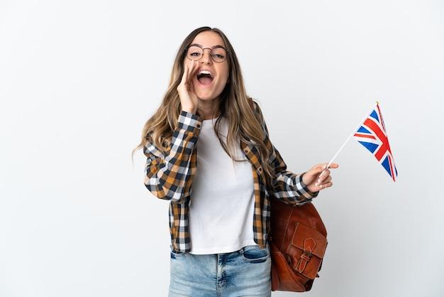 Giovane donna rumena che tiene una bandiera del regno unito isolata sul muro bianco che grida con la bocca spalancata