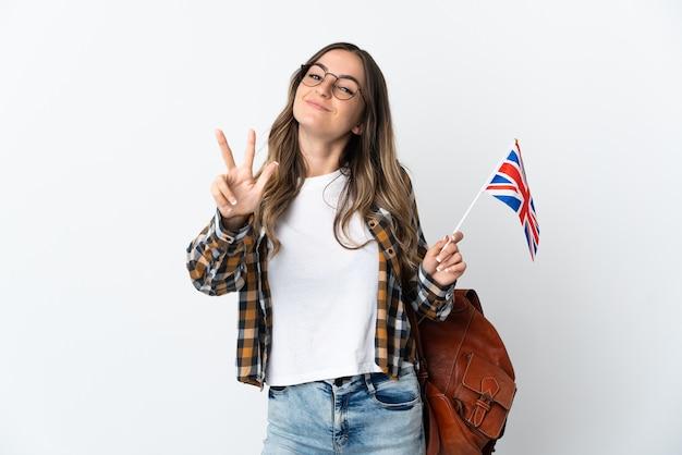 Giovane donna rumena che tiene una bandiera del regno unito su bianco felice e che conta tre con le dita