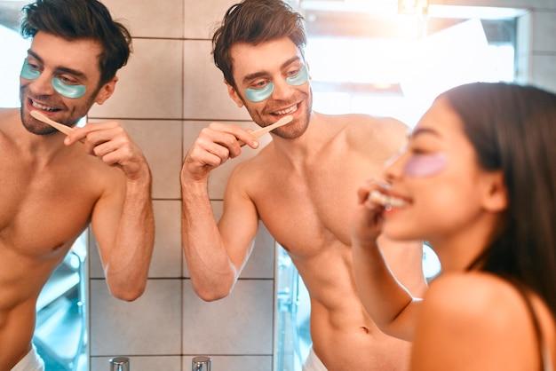 Una giovane coppia romantica in bagno si lava i denti davanti allo specchio e si incolla dei cerotti idratanti sotto gli occhi, divertendosi insieme. routine mattutina, cura della pelle del viso e del corpo.