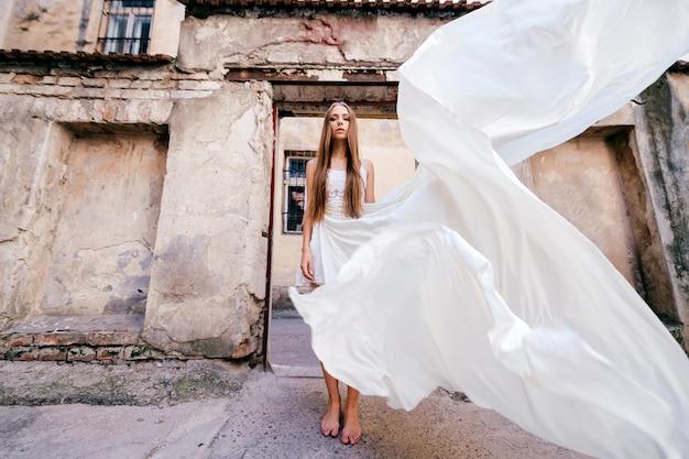 Giovane ragazza elegante romantica in abito bianco lungo volo in posa su antichi edifici in pietra
