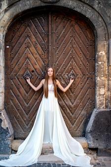Giovane ragazza elegante romantica in vestito bianco lungo che posa sopra la porta antica