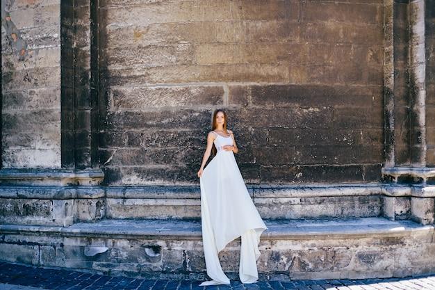Giovane ragazza elegante romantica in vestito bianco lungo che posa sopra il muro antico di pietra