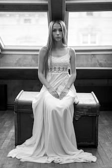 Giovane ragazza elegante romantica in abito bianco lungo seduto sul petto nel soppalco