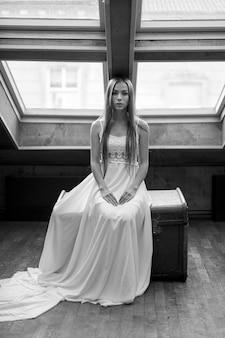 Giovane ragazza elegante romantica in vestito bianco lungo che si siede sul petto nel soppalco