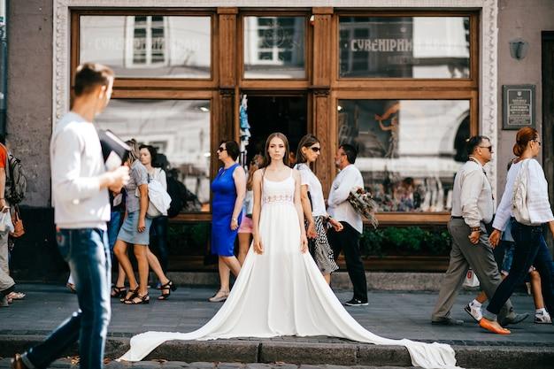 Giovane ragazza elegante romantica in abito bianco lungo in piedi sulla strada affollata