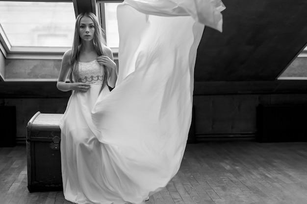 Giovane ragazza elegante romantica in abito bianco lungo galleggiante seduto sul petto dower nel loft