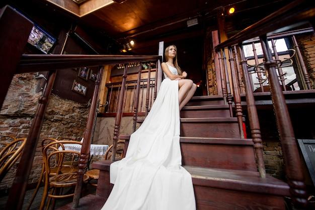 Giovane ragazza elegante romantica in abito lungo bianco fluido in posa sulle scale al coperto