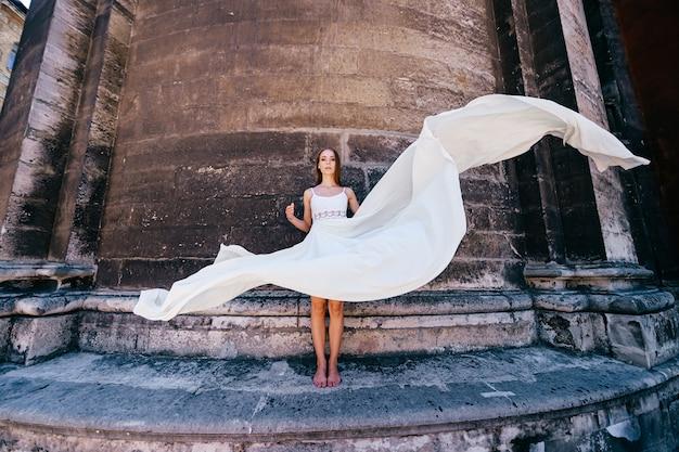 Giovane ragazza elegante romantica in vestito fluido bianco lungo che posa sopra il muro antico di pietra