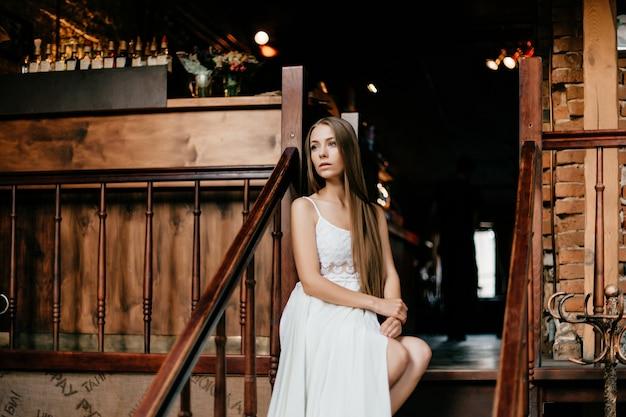 Giovane ragazza premurosa romantica in vestito bianco lungo che si siede sulle scale