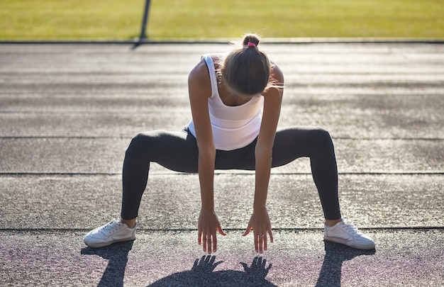 Giovane corridore in forma donna streching prima di esercizi all'aperto