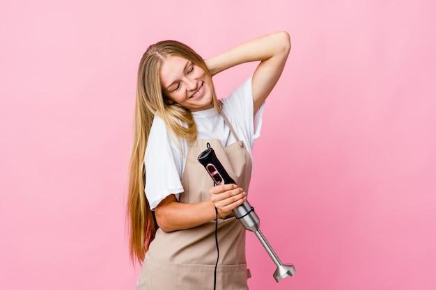 La giovane donna russa del cuoco che tiene un miscelatore elettrico ha isolato ballando e divertendosi.