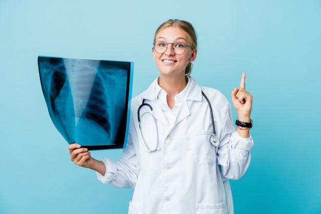 La giovane donna russa del medico che tiene una scintigrafia ossea sul blu indica con entrambe le dita anteriori in su mostrando uno spazio vuoto.