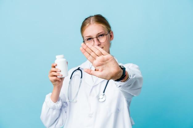 La giovane donna russa del medico che tiene la bottiglia delle pillole sull'azzurro che fa un gesto di diniego