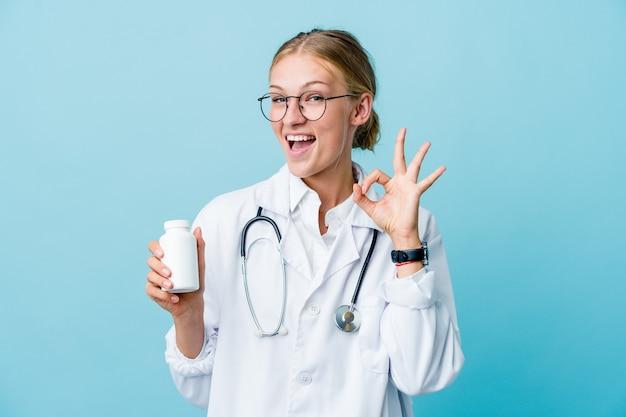 La giovane donna russa del medico che tiene la bottiglia delle pillole sull'azzurro strizza l'occhio e tiene un gesto giusto con la mano.
