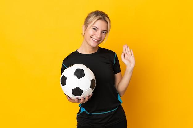 Giovane donna russa del giocatore di football americano isolata su fondo giallo che saluta con la mano con l'espressione felice