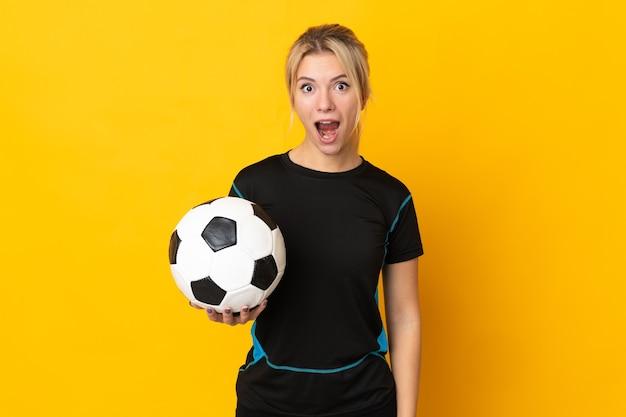 Giovane donna russa del giocatore di football americano isolata su fondo giallo con l'espressione facciale di sorpresa