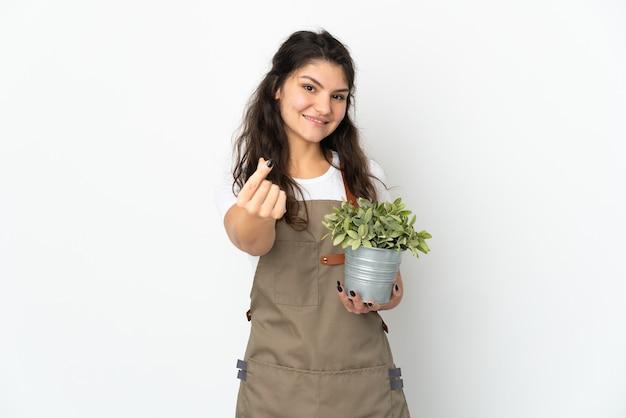 Giovane ragazza russa del giardiniere che tiene una pianta isolata facendo il gesto dei soldi