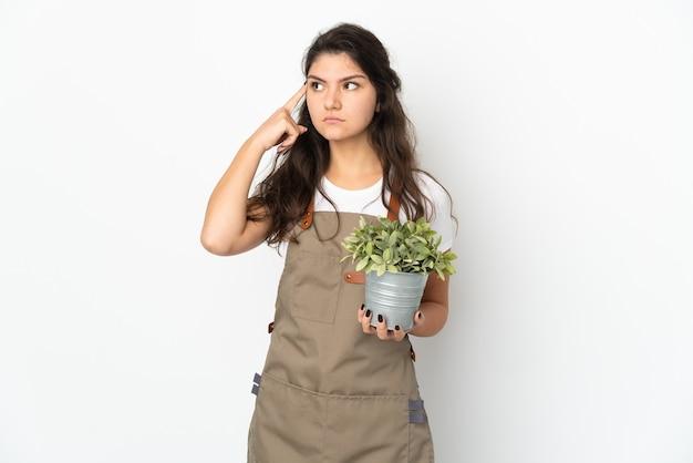 Giovane ragazza russa del giardiniere che tiene una pianta isolata