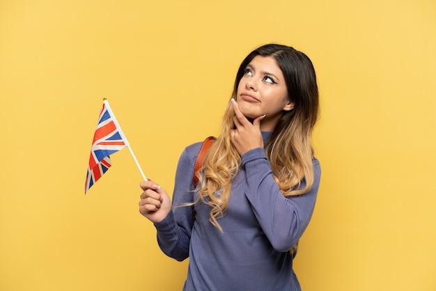 Giovane ragazza russa in possesso di una bandiera del regno unito isolata su sfondo giallo che ha dubbi mentre guarda in alto