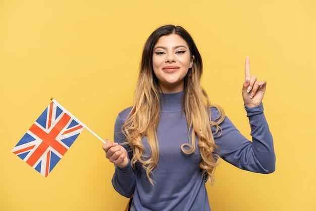 Giovane ragazza russa in possesso di una bandiera del regno unito isolata su sfondo giallo che indica una grande idea