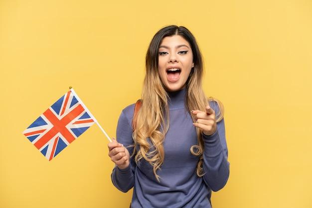 Giovane ragazza russa in possesso di una bandiera del regno unito isolata su sfondo giallo sorpreso e rivolto verso la parte anteriore