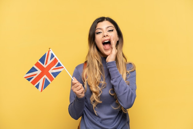 Giovane ragazza russa in possesso di una bandiera del regno unito isolata su sfondo giallo con espressione facciale sorpresa e scioccata