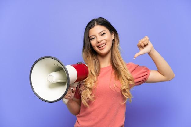 Giovane ragazza russa isolata su sfondo blu con in mano un megafono e orgogliosa e soddisfatta di sé