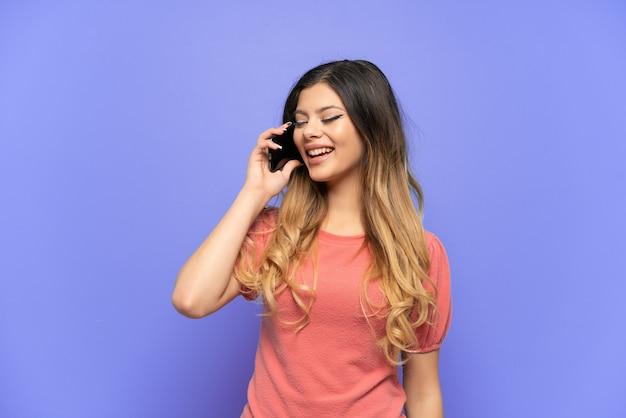 Giovane ragazza russa isolata su sfondo blu che tiene una conversazione con il telefono cellulare con qualcuno