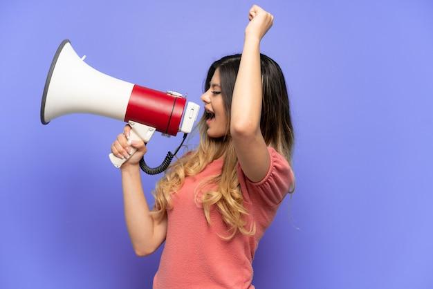 Giovane ragazza russa isolata su sfondo blu che grida attraverso un megafono per annunciare qualcosa in posizione laterale