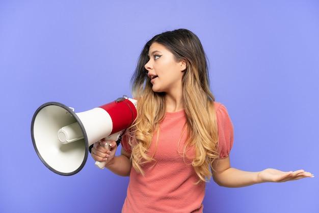 Giovane ragazza russa isolata sulla parete blu che tiene un megafono e con l'espressione facciale di sorpresa