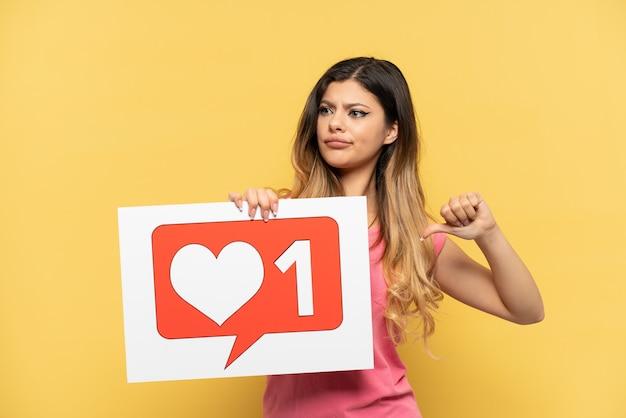 Giovane ragazza russa isolata su sfondo giallo con in mano un cartello con l'icona mi piace e che punta in avanti