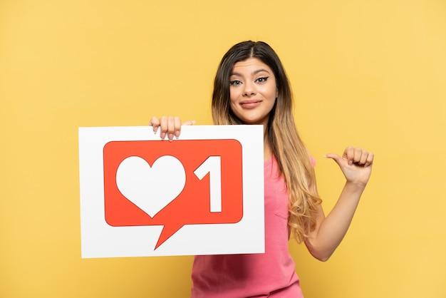 Giovane ragazza russa isolata su sfondo giallo in possesso di un cartello con l'icona mi piace con gesto orgoglioso