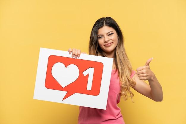 Giovane ragazza russa isolata su sfondo giallo in possesso di un cartello con l'icona mi piace con il pollice in alto