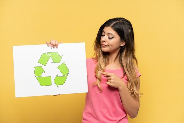 Giovane ragazza russa isolata su sfondo giallo che tiene in mano un cartello con l'icona di riciclo e lo indica