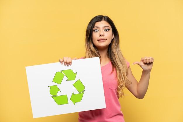 Giovane ragazza russa isolata su sfondo giallo in possesso di un cartello con icona di riciclo con gesto orgoglioso