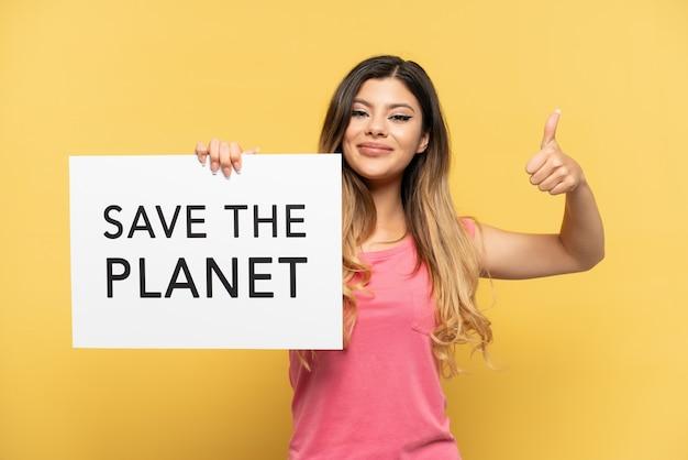 Giovane ragazza russa isolata su sfondo giallo che tiene un cartello con il testo salva il pianeta con il pollice in su
