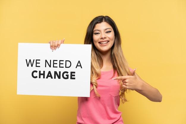Giovane ragazza russa isolata su sfondo giallo che tiene un cartello con il testo abbiamo bisogno di un cambiamento e lo indica
