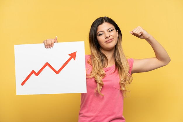 Giovane ragazza russa isolata su sfondo giallo con in mano un cartello con un simbolo di freccia statistica in crescita e facendo un gesto forte