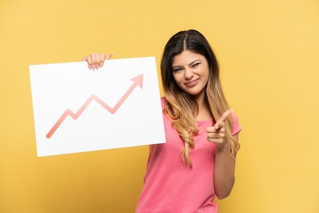 Giovane ragazza russa isolata su sfondo giallo con in mano un cartello con un simbolo di freccia statistica in crescita e rivolto verso la parte anteriore