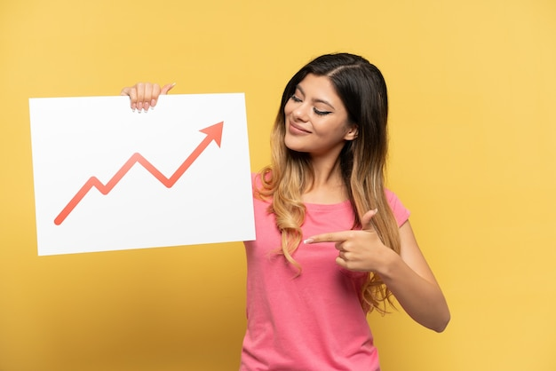 Giovane ragazza russa isolata su sfondo giallo con in mano un cartello con un simbolo di freccia statistica in crescita e che lo punta