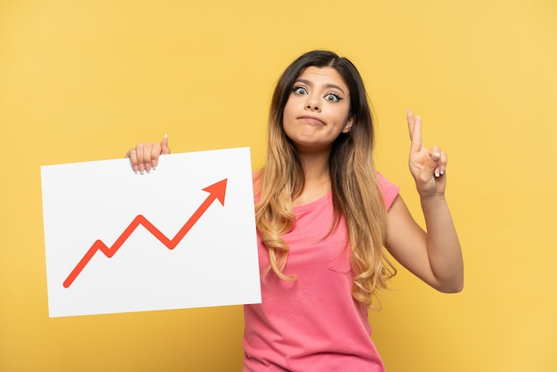 Giovane ragazza russa isolata su sfondo giallo con in mano un cartello con un simbolo di freccia statistica in crescita con le dita incrociate