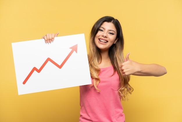 Giovane ragazza russa isolata su sfondo giallo con in mano un cartello con un simbolo di freccia di statistiche in crescita con il pollice in su