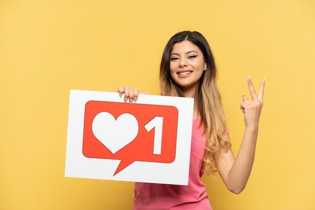 Giovane ragazza russa isolata sulla parete gialla che tiene un cartello con l'icona like e celebra una vittoria