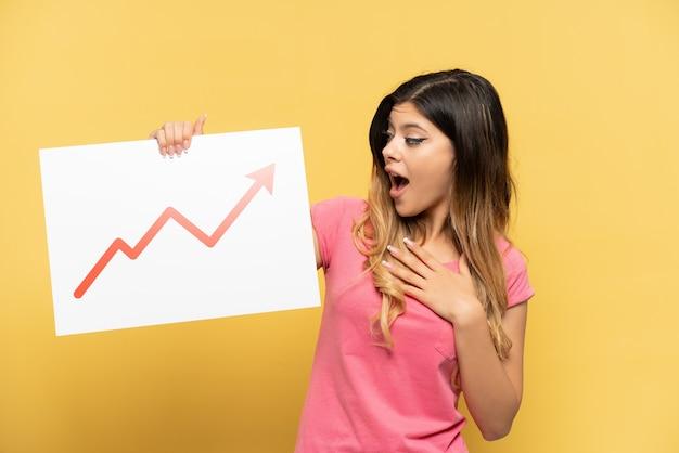 Giovane ragazza russa isolata sul muro giallo con in mano un cartello con un simbolo di freccia statistica in crescita e celebrando una vittoria