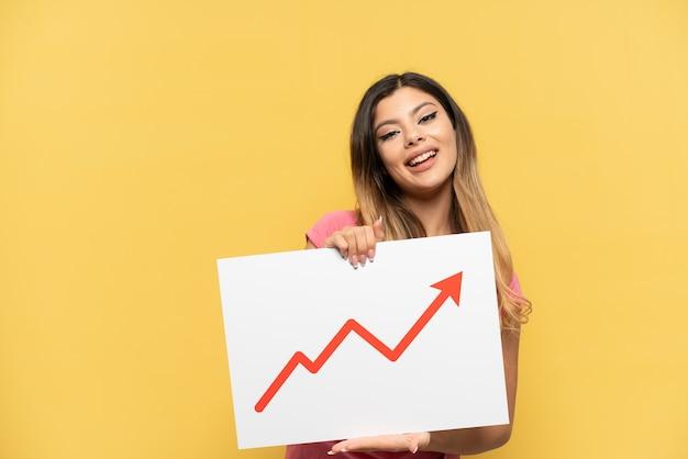 Giovane ragazza russa isolata sul muro giallo con in mano un cartello con un simbolo di freccia statistica in crescita con espressione felice