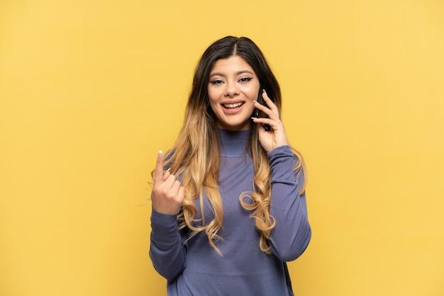 Giovane ragazza russa che utilizza il telefono cellulare isolato su sfondo giallo facendo un gesto imminente