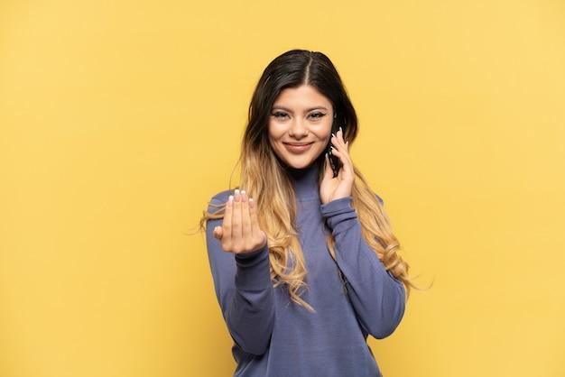 Giovane ragazza russa che utilizza il telefono cellulare isolato su sfondo giallo che invita a venire con la mano. felice che tu sia venuto