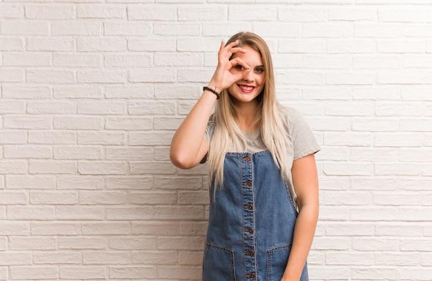 Giovane donna russa dei pantaloni a vita bassa fiduciosa che fa gesto giusto sull'occhio